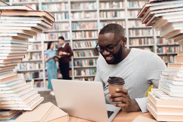 Ethnischer afrikaner benutzt laptop und trinkt kaffee.