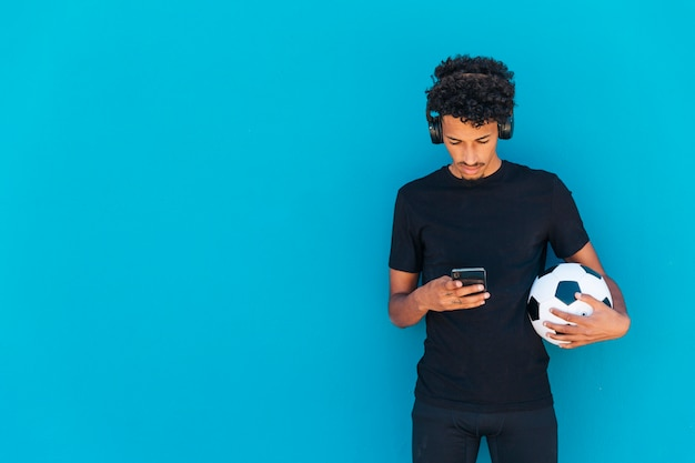 Ethnischer gelockter athlet, der fußball hält und telefon verwendet