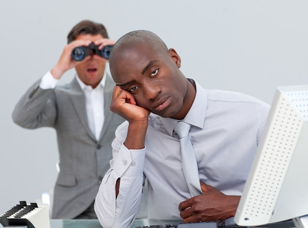 Ethnischer geschäftsmann, der gelangweilt wird und sein manager, der durch ferngläser schaut