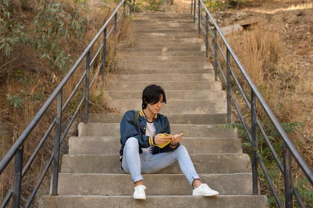 Ethnischer jugendlicher, der mit buch auf treppen sitzt