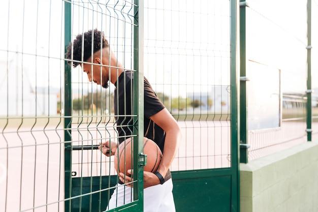 Ethnischer junger mann, der basketballplatz betritt