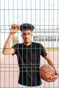 Ethnischer junger mann mit basketball hinter zaun