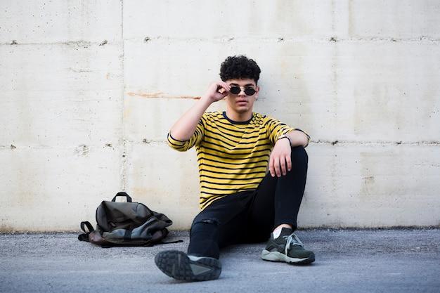 Ethnischer junger mann mit der kühlen frisur, die auf asphalt sitzt