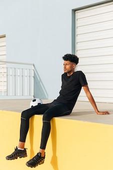 Ethnischer junger mit fußball sitzender und träumender mann