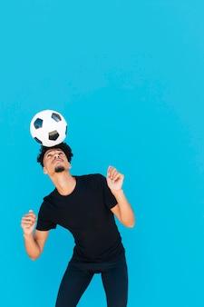 Ethnischer kerl mit dem lockigen haar, das mit fußball ausübt