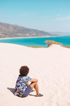 Ethnischer mann, der auf sandigem strand sitzt