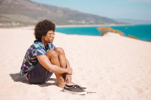 Ethnischer mann, der barfuß auf sandigem strand sitzt
