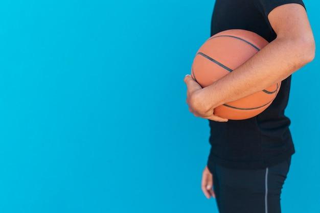 Ethnischer mann, der basketball hält