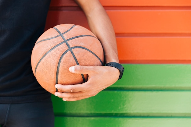 Ethnischer mann der ernte, der basketball hält