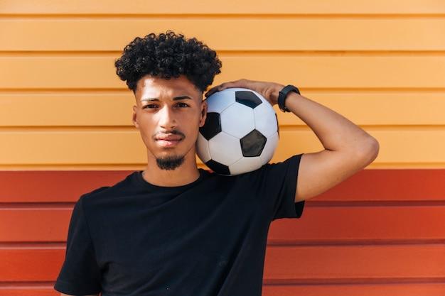 Ethnischer mann, der fußball auf schulter hält