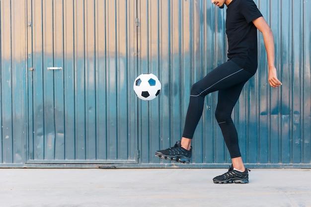 Ethnischer mann, der fußball auf straße spielt