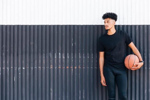Ethnischer mann mit dem basketball, der weg schaut