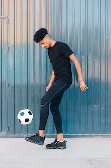 Ethnischer sportler, der fußball auf straße tritt