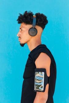 Ethnischer sportler, der kopfhörer mit telefon in der armbinde verwendet