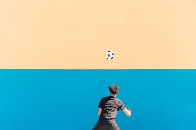 Ethnischer sportler mit dem gelockten haar, das fußball wirft