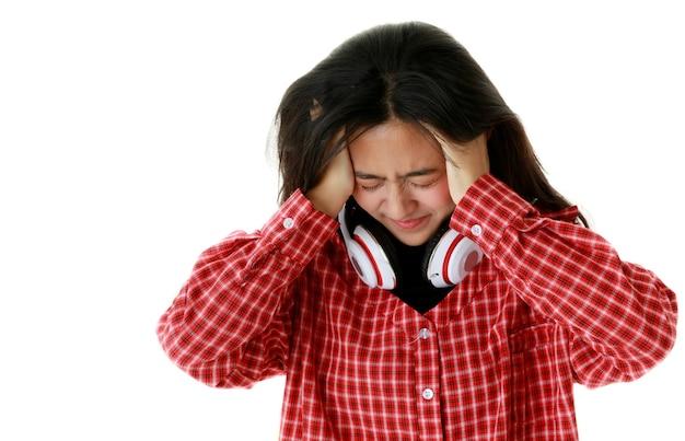 Ethnischer weiblicher hipster mit kopfhörern am hals, der den kopf berührt und an migräne auf weißem, isoliertem hintergrund leidet.