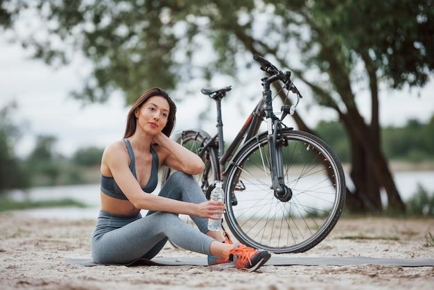 Etwas frisches wasser. weibliche radfahrerin mit guter körperform, die tagsüber nahe ihrem fahrrad am strand sitzt