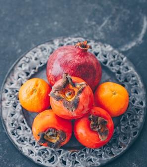 Etwas granatapfel und persimone mit mandarine in metallplatte auf dunkler, hoher winkelansicht.