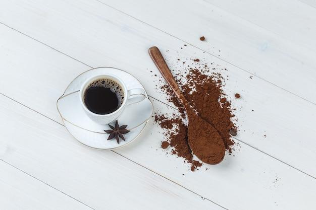 Etwas kaffee mit gemahlenem kaffee, gewürze in einer tasse auf holzhintergrund, flach liegen.