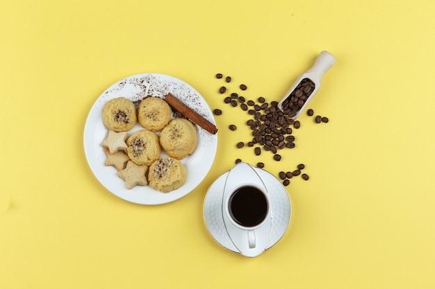 Etwas kaffee mit kaffeebohnen, keksen, zimtstange auf gelbem hintergrund