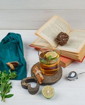 Etwas kräutertee und zimt mit büchern, zitrone, gewürzen und grünem schal auf einem holzbrett