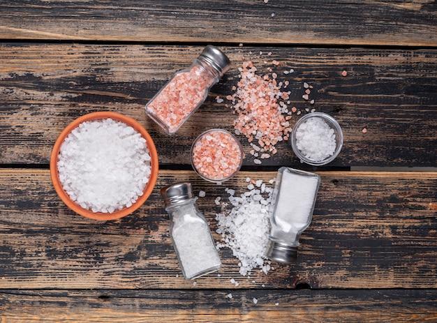 Etwas meersalz und himalaya-salz in schalen und aus salzstreuern