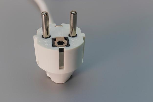 Eu-stecker auf grauem hintergrund. elektriker zu hause. nahansicht. voller fokus. platz kopieren.