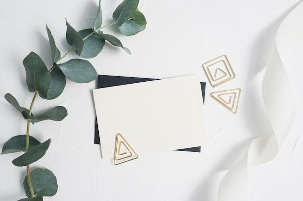 Eukalyptusblätter und dekorbüroklammer mit leerer visitenkarte oder grußkarte