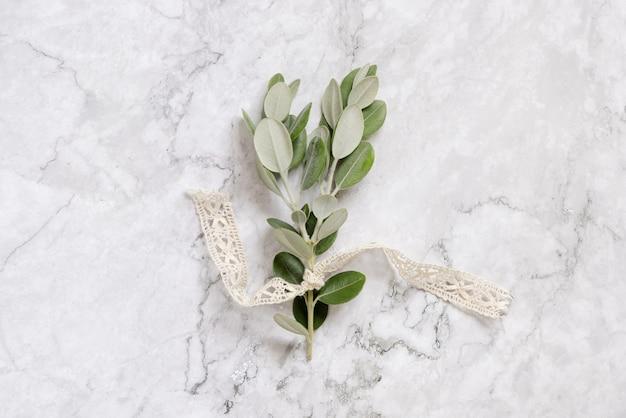 Eukalyptuszweig mit vintage-band auf weißem marmortisch, draufsicht