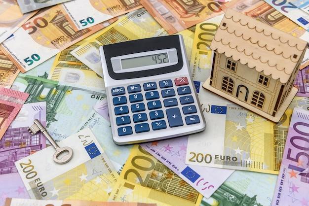 Euro-banknoten als hintergrund für kleines spielzeughaus