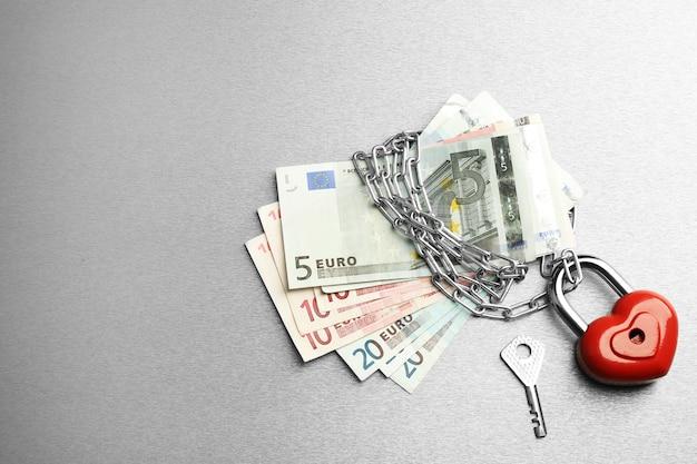 Euro-banknoten mit schloss und kette auf grauer oberfläche