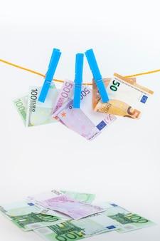 Euro-banknoten mit wäscheklammern an einem seil auf weißem isoliertem hintergrund befestigt