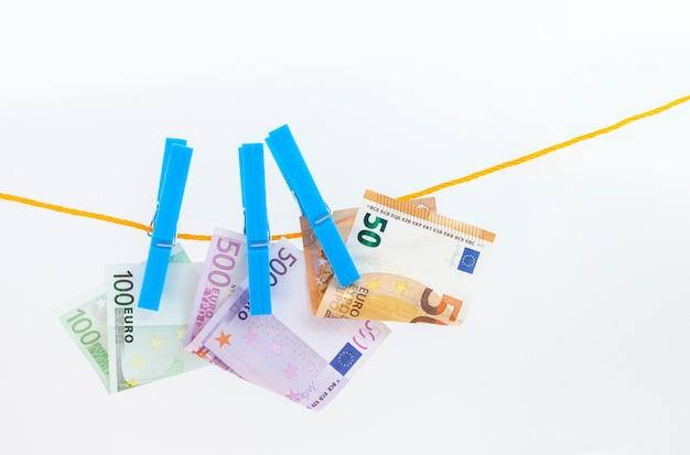 Euro-banknoten mit wäscheklammern an einem seil auf weißem, isoliertem hintergrund befestigt
