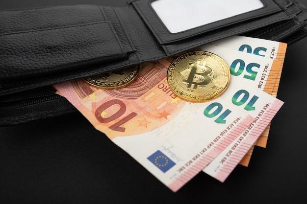 Euro-banknoten und bitcoins in einer brieftasche