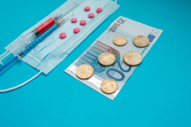 Euro-banknoten und -münzen. medizinische maske, impfstoffspritze und rosa pillen. wirtschaftskrise. gesundheitsausgaben. ausbruch des coronavirus.