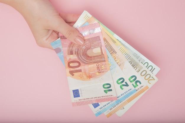 Euro-banknotengeld in den weiblichen händen auf rosa hintergrund. geschäftskonzept und instagram