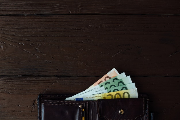 Euro bargeld. öffnen sie braune männliche geldbörse mit eurobanknoten auf hölzernem hintergrund