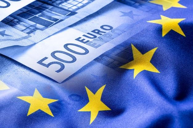 Euro-flagge. euro-geld. euro währung. bunte wehende flagge der europäischen union auf einem euro-geld-hintergrund.