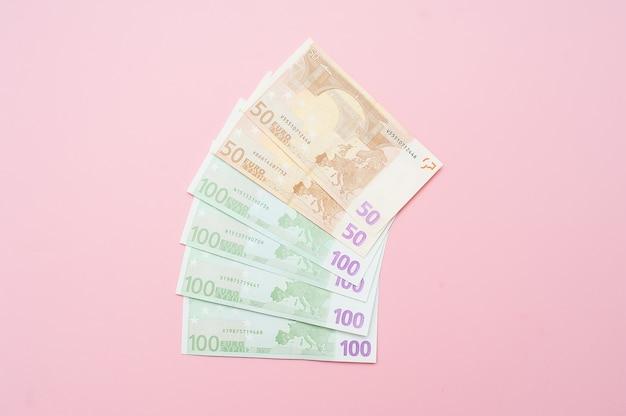 Euro geld fächerförmig. abschluss oben der banknote auf pastellrosahintergrund.