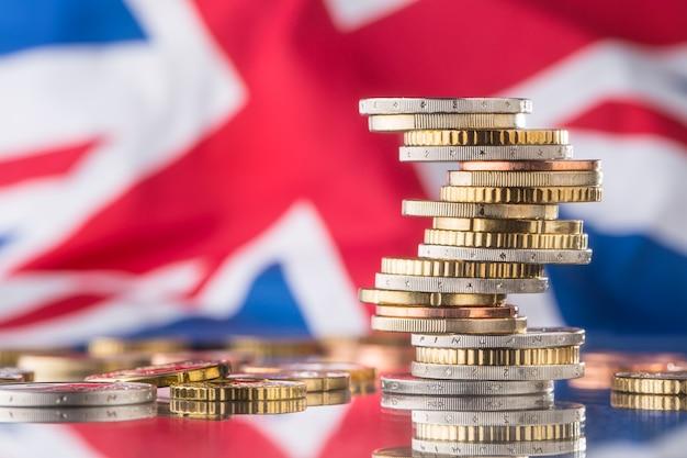 Euro-münzen eine flagge des vereinigten königreichs im hintergrund. finanzielles konzept.