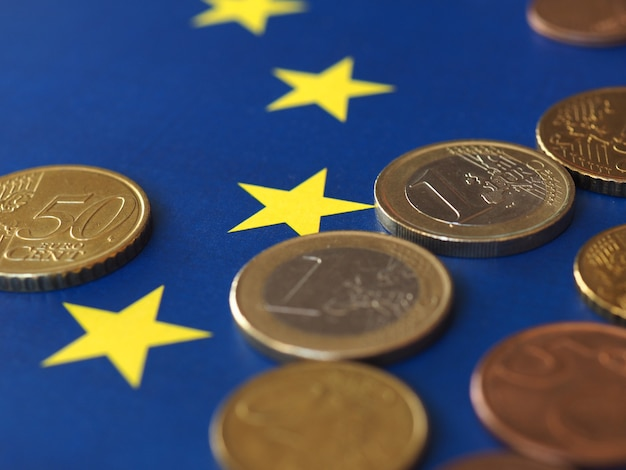 Euro-münzen (eur), währung der europäischen union über der flagge europas