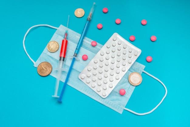 Euro-münzen. medizinische maske, impfstoffspritze und rosa pillen, pillenblase. wirtschaftskrise. gesundheitsausgaben. ausbruch des coronavirus.