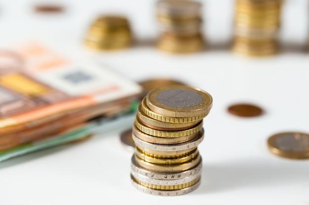 Euro-münzen stehen in der spalte auf weißem tisch mit haufen von banknoten im hintergrund.
