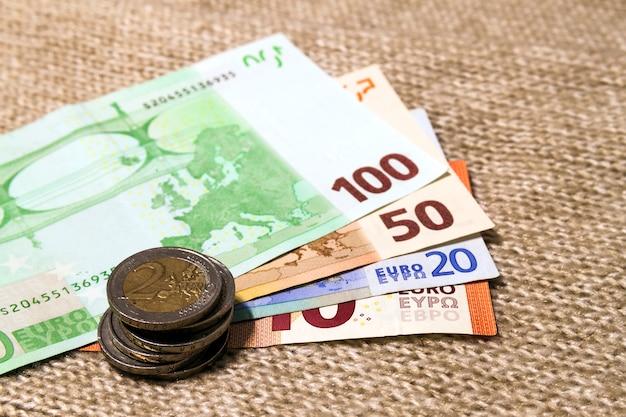 Euro-münzen und banknoten in verschiedenen positionen aufeinander gestapelt
