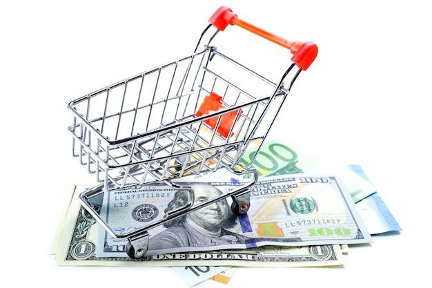 Euro- und us-dollar-banknoten mit einkaufswagen: finanzkonzept