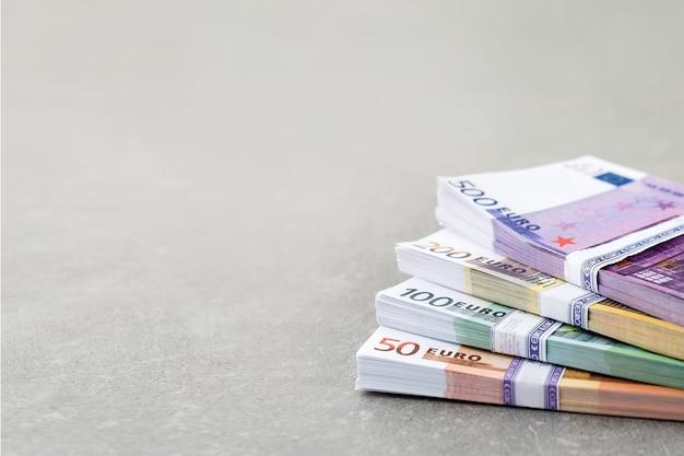 Euro-währungsgeld. bargeld, euro-rechnungen. stapel von euro-banknoten auf konkretem hintergrund in fünfhundert, zweihundert, einhundert und fünfziger jahren. copyspace für text.