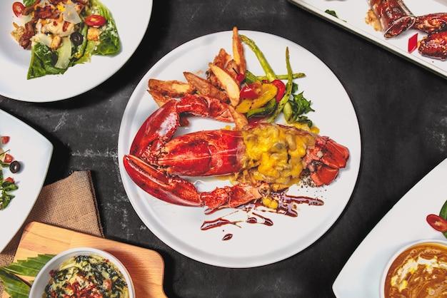 Europa essen essen gesetzt gut vorbereiten. mit maine hummer, caesar salat, hühnerflügel, gebackener spinat, kürbissuppe.