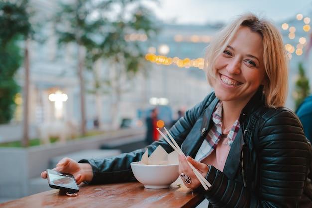 Europäische blonde frau, die reis pho bo mit vietnamesischem café der hölzernen stocktabellenstraße in moskau isst.