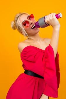 Europäische blonde sängerin in einem leuchtend roten kleid mit maniküre mit einem mikrofon in den händen auf einer gelben studiooberfläche