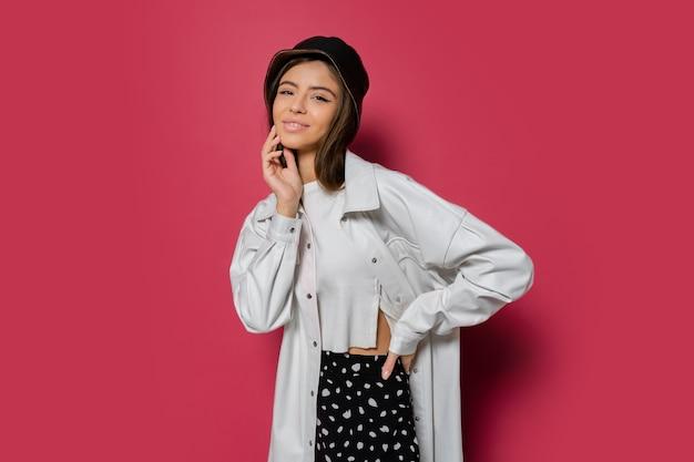 Europäische brünette frau im schwarzen panama und in der weißen trendigen jacke, die auf rosa hintergrundisolat aufwirft.